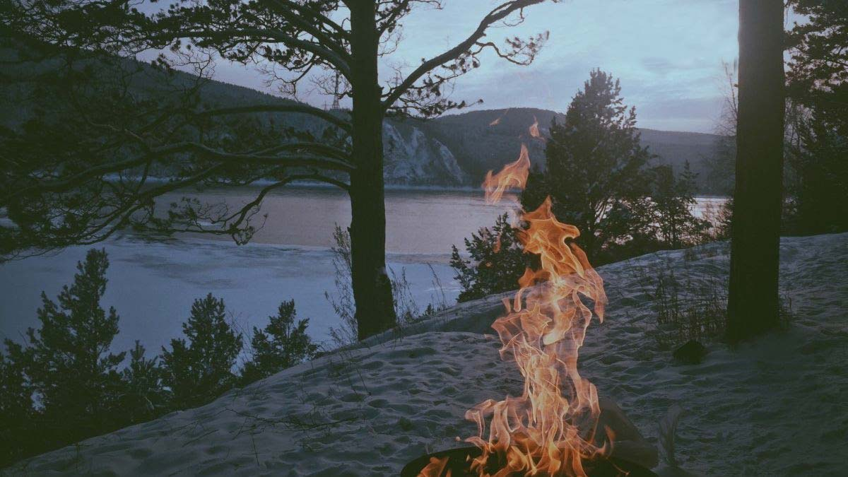 A lake with a campfire at dusk